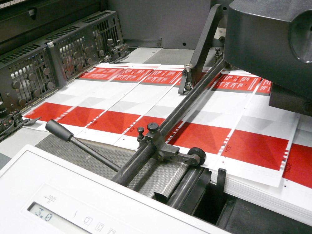 Medientechnologe Druck - Die Druckbogen laufen in die Druckmaschine ein.