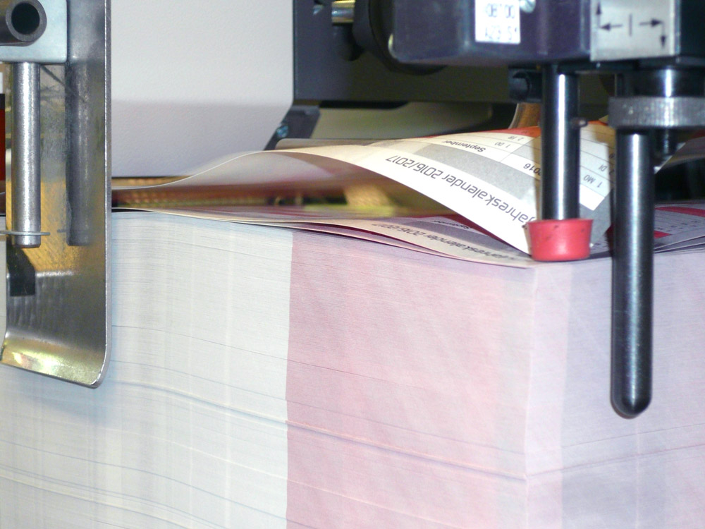 Medientechnologe Druckverarbeitung- Die Falzbogen werden im Anleger der Falzmaschine gestapelt.