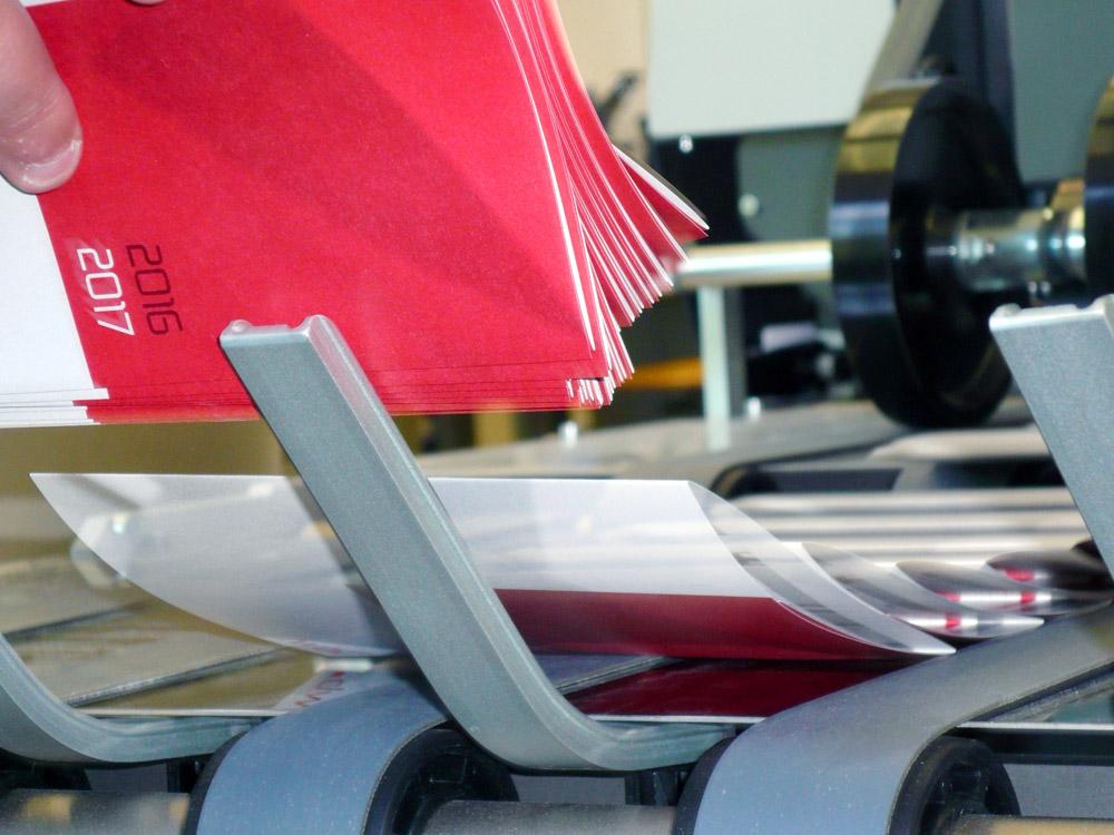 Medientechnologe Druckverarbeitung- Die fertigen Kalender werden stapelweise entnommen.