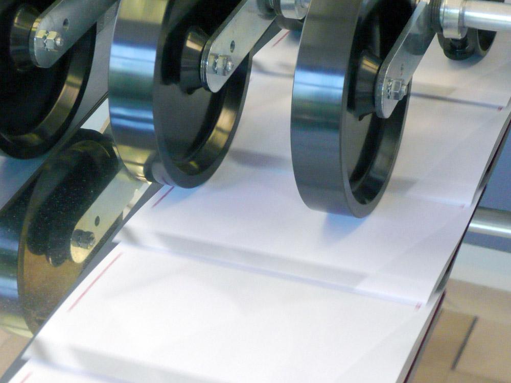 Medientechnologe Druckverarbeitung- Die fertig gefalzten Kalender laufen in  den Ausleger ein.