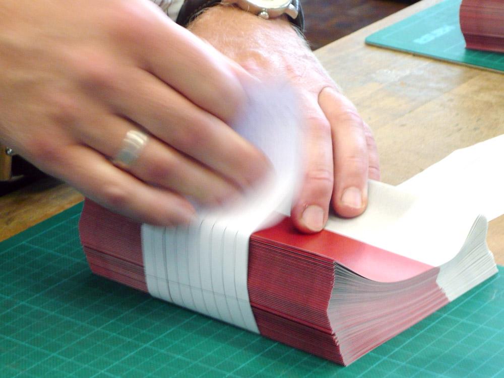 Medientechnologe Druckverarbeitung - Die fertigen Kalender werden mit einer Banderole in kleine Päckchen gebündelt.