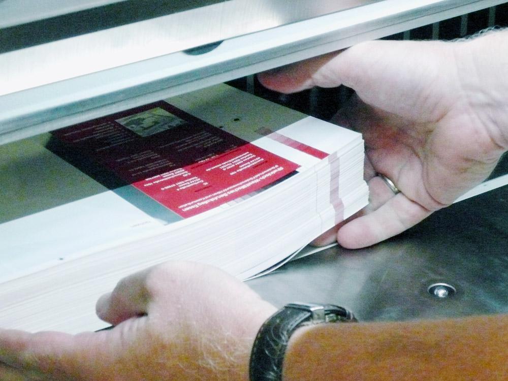 Medientechnologe Druckverarbeitung -  Die Bogen werden in die Schneidemaschine gelegt.