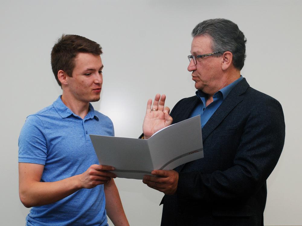 Der Absolvent (Industriemechaniker) erhält sein Abschlusszeugnis aus den Händen des stellvertretenden Schulleiters Franjo Görgen.