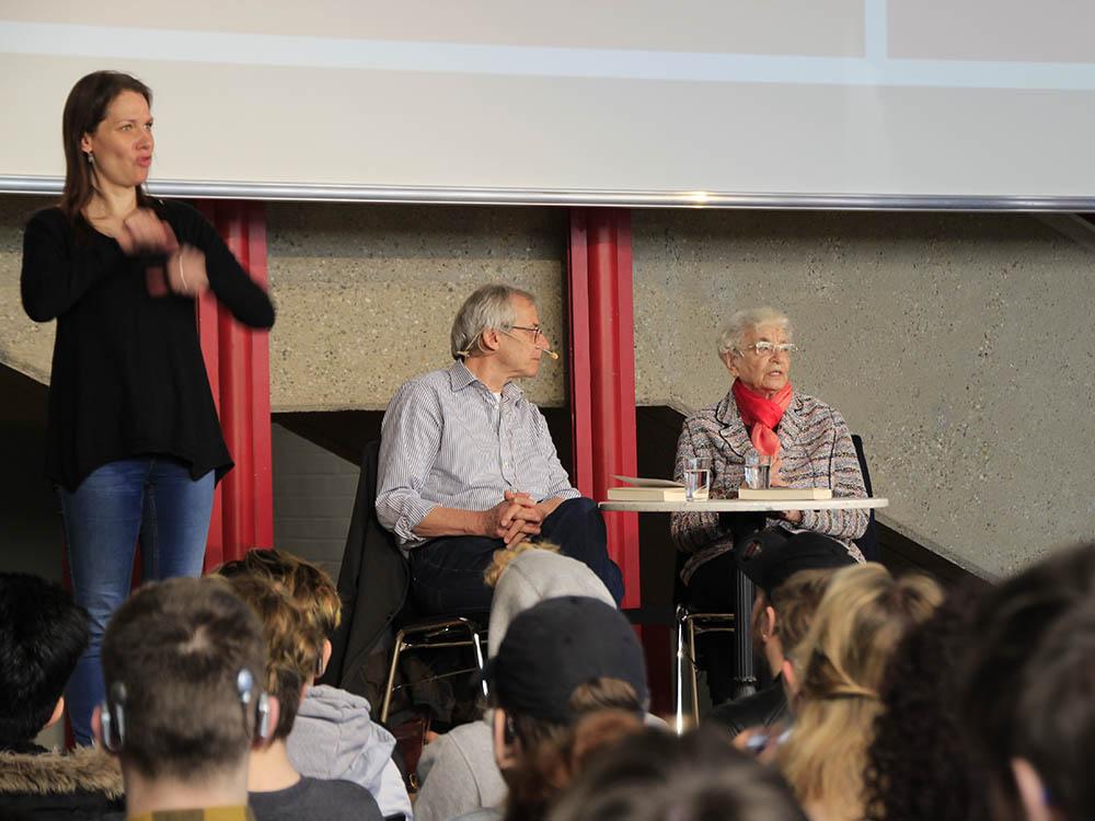 RWB Essen - Besuch der Zeitzeugin des Nationalsozialismus Ruth Weiss - Ruth Weiss erzählt von ihren Erlebnissen im Nationalsozialismus. Lutz Kliche (Mitte) moderiert die Veranstaltung. Judith Zeus (links) ist Gebärdensprachdolmetscherin und übersetzt alles in die Deutsche Gebärdensprache.