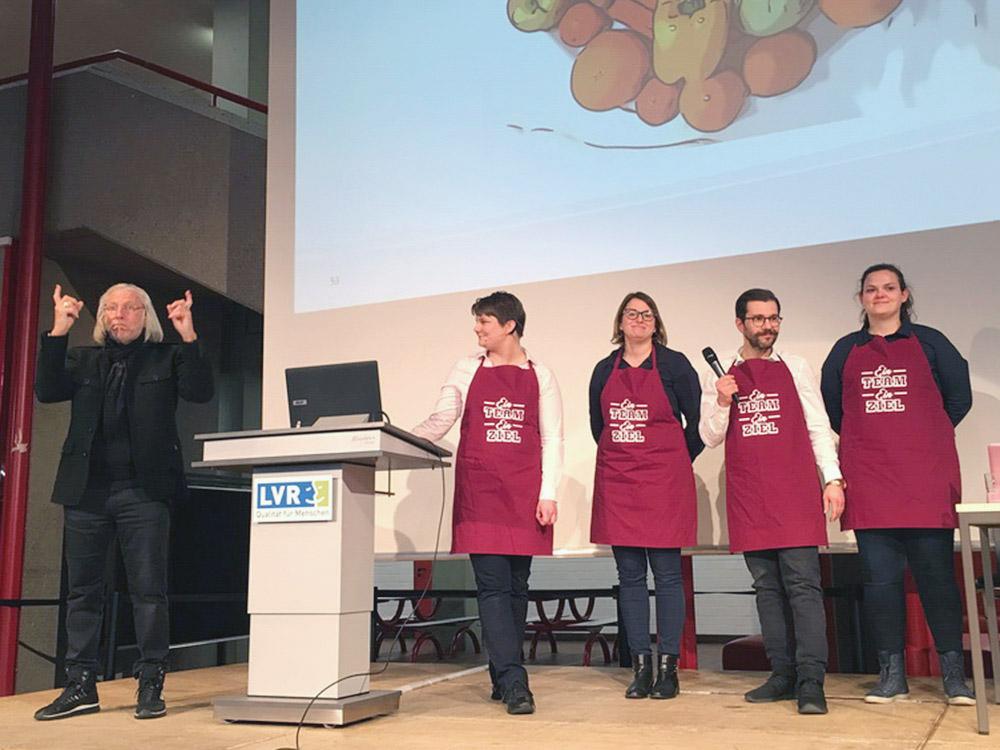"""RWB Essen - Präsentation der Abschlussprojekte der Fachschule Wirtschaft - Die Projektgruppe """"Veggie-Bus"""" vor dem Logo des Projektes."""