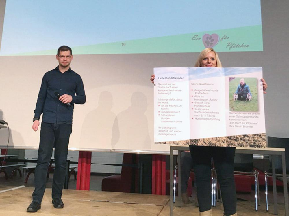 """RWB Essen - Präsentation der Abschlussprojekte der Fachschule Wirtschaft -  Die Projektgruppe """"Mobiler Gassi-Service"""" stellt ihren Flyer als  eines der Werbemittel vor."""