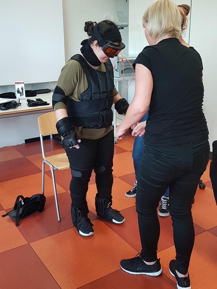 RWB Essen - Projekttag in der Berufsfachschule Gesundheit - Alterssimulation - Das Anlegen des Anzugs ist schon anstrengend.