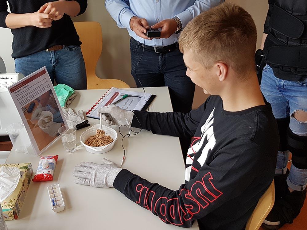 """RWB Essen - Projekttag in der Berufsfachschule Gesundheit - Alterssimulation - Die alltäglichen Dinge wie zum Beispiel """"Das ruhige Halten eines Löffels beim Essen"""" werden zu einer schwierigen Aufgabe."""