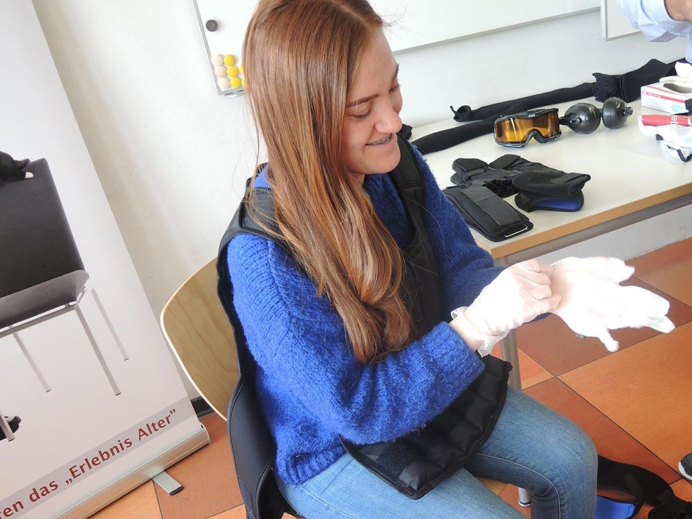 RWB Essen - Projekttag in der Berufsfachschule Gesundheit - Alterssimulation - Aus hygienischen Gründen müssen zuerst Schutzhandschuhe angezogen werden.