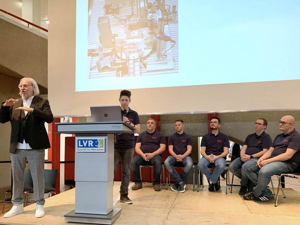 RWB Essen - Fachschule Automatisierungstechnik - Präsentation der Abschlussprojekte - Gruppe 1 - Eine Studierende erklärt die Mechanik am Beispiel des Drehtellers.
