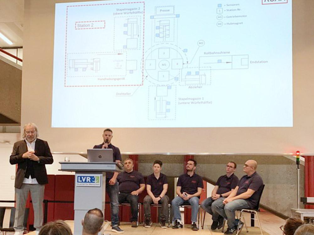 RWB Essen - Fachschule Automatisierungstechnik - Präsentation der Abschlussprojekte - Gruppe 1 - Ein Studierender stellt den Aufbau der Mechanik dar.
