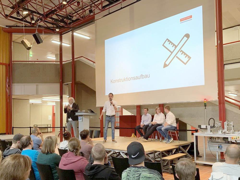 RWB Essen - Fachschule Automatisierungstechnik - Präsentation der Abschlussprojekte - Gruppe 2 - Ein Studierender erklärt den Konstruktionsaufbau.