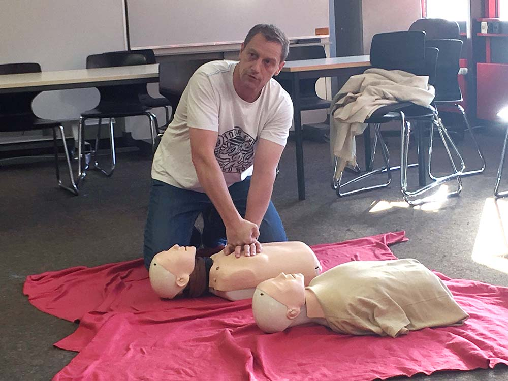 """RWB Essen- Schultour """"Leben retten – auch im Sport"""" -  Der Kursleiter führt an einem Dummy die Herzdruckmassage vor."""