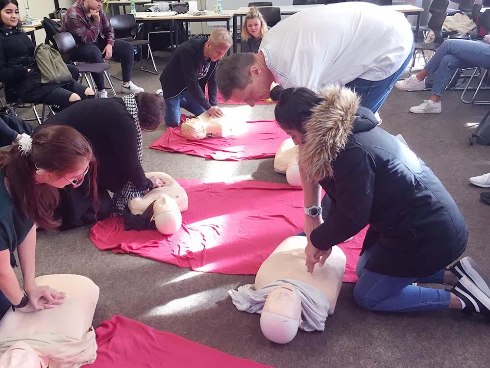 """RWB Essen- Schultour """"Leben retten – auch im Sport"""" -  Die Schülerinnen und Schüler üben an einem Dummy die Herzdruckmassage."""