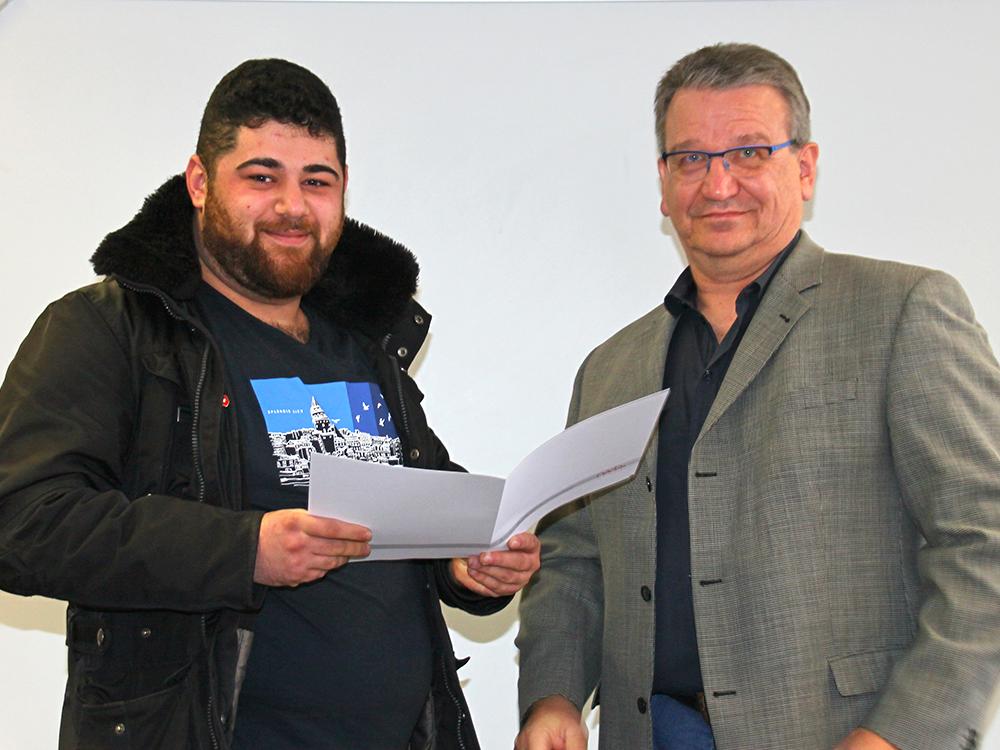 RWB Essen - Abschlussfeier der Abteilung Technik - 3,5 jährige Ausbildungsberufe -  Salih Güner erhält sein Abschlusszeugnis vom stellvertretenden Schulleiter Herrn Görgen.