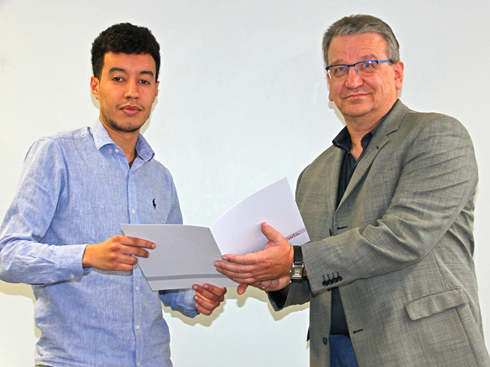 RWB Essen - Abschlussfeier der Abteilung Technik - 3,5 jährige Ausbildungsberufe - Ali Nmili erhält sein Abschlusszeugnis vom stellvertretenden Schulleiter Herrn Görgen.