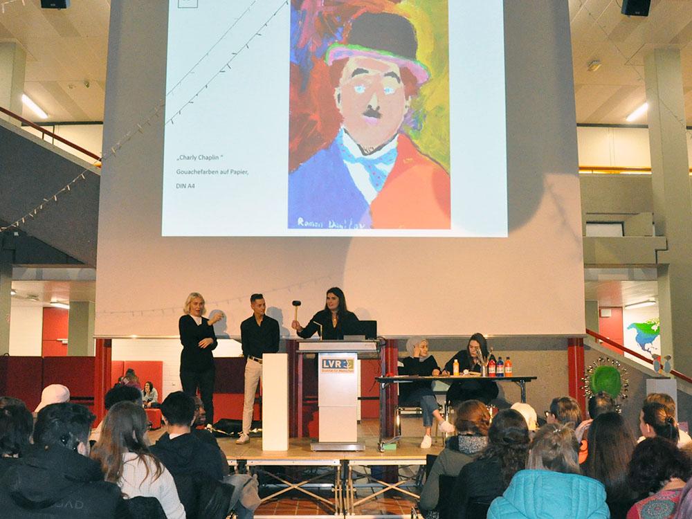 RWB Essen - Kunstauktion 2019 - Das Moderatoren-Team und die Dolmetscherin stellen die Kunstwerke vor.