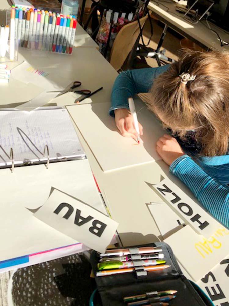 """RWB Essen - Projekt """"Abteilung Technik in einem Schaufenster"""" -  Die Schülerin gestaltet die Beschriftuung für die Kästen des Regals."""