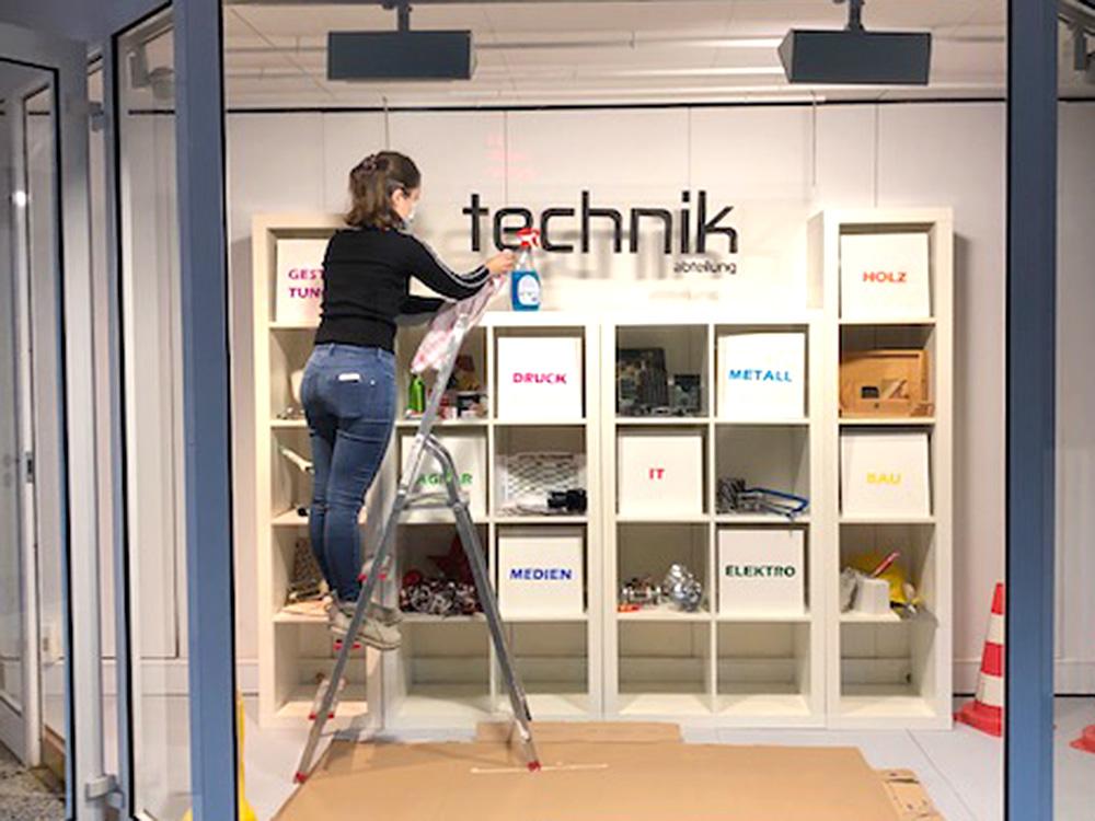 """RWB Essen - Projekt """"Abteilung Technik in einem Schaufenster"""" - Die Schülerin erledigt die letzten Arbeiten für das Schaufenster."""